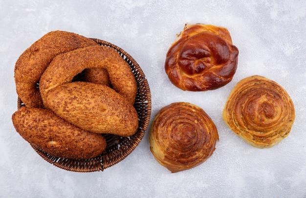 Vista superior de pães frescos, como rissóis bagels em um balde em um fundo branco