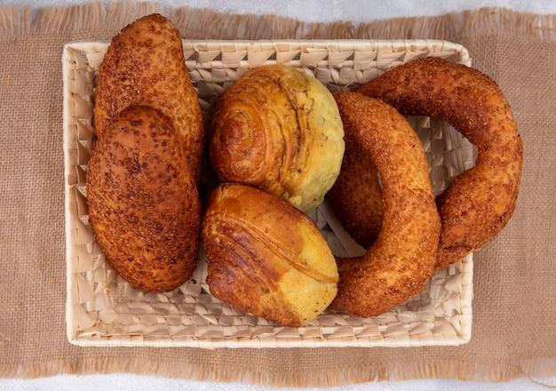 Vista superior de pães frescos em um balde em um pano de saco em um fundo branco