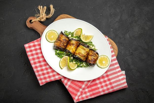 Vista superior de pãezinhos de berinjela salgados prato cozido com rodelas de limão na mesa escura jantar cozinhando prato de óleo cítrico