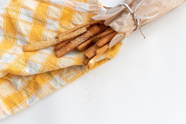 Vista superior de palitos de pão de grissini com sementes de gergelim em um saco de papel com um laço em um fundo claro