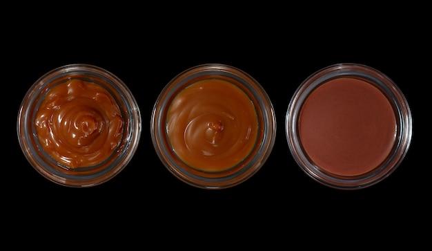 Vista superior de panelas com caramelo, manteiga de cacau e óleo de chocolate