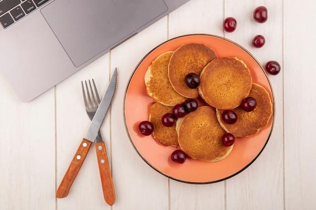 Vista superior de panquecas com cerejas no prato e faca de garfo e bloco de notas no fundo de madeira