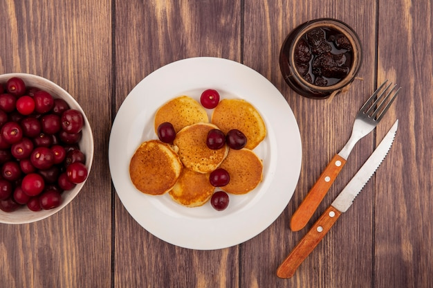 Vista superior de panquecas com cerejas no prato e tigela de cereja com geleia de morango e garfo faca no fundo de madeira