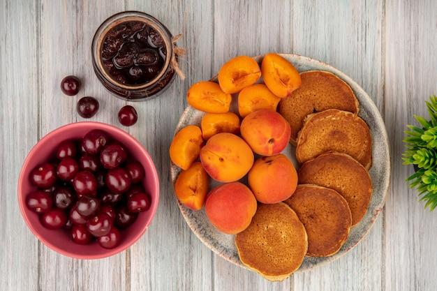 Vista superior de panquecas com damascos inteiros e fatiados em prato e tigela de cerejas com geleia de morango no fundo de madeira