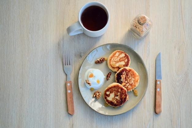 Vista superior de panquecas de queijo caseiro syrniki com creme de leite e xícara de chá
