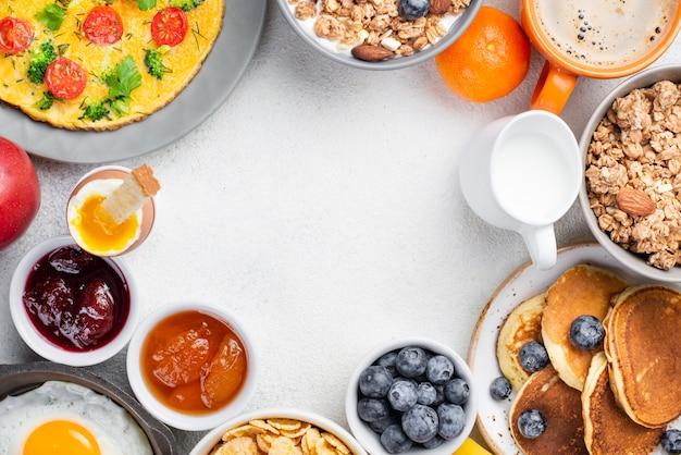 Vista superior de panquecas e omelete com geléia e mirtilos no café da manhã
