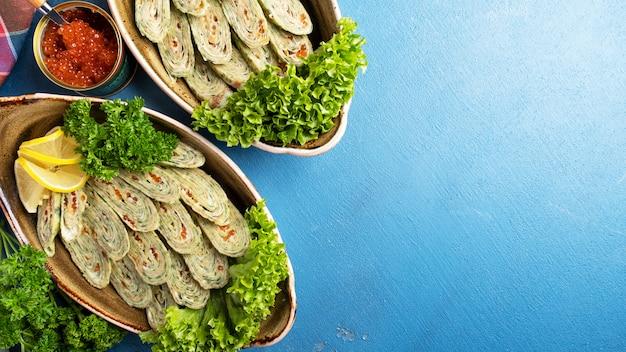 Vista superior de panquecas fininhas com espinafre e caviar.