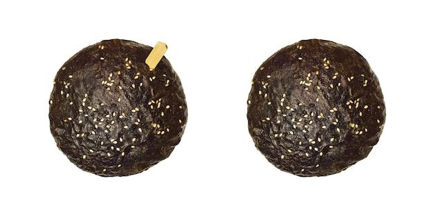 Vista superior de pão escuro de hambúrguer ou pão com sementes de gergelim e uma vara de madeira isolada no fundo branco