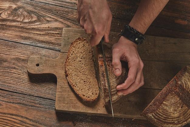 Vista superior de pão fresco cortado nas mãos de um homem em uma placa de madeira ao fundo