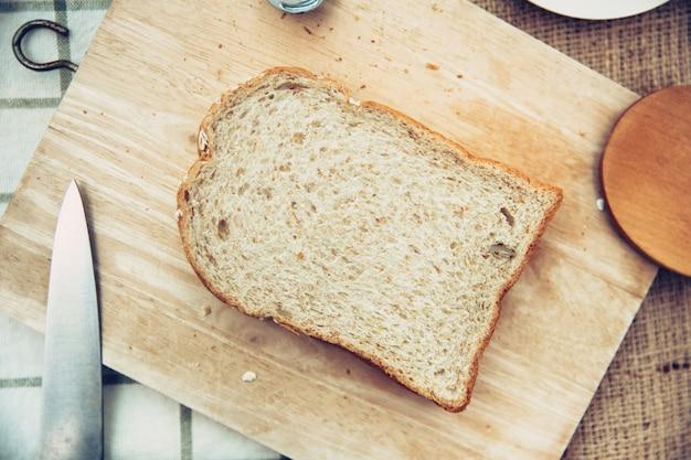 Vista superior de pão integral de trigo rústico na mesa de madeira vintage colortone