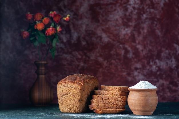 Vista superior de pão preto dietético cortado inteiro e farinha em um vaso de flores sobre fundo azul marrom