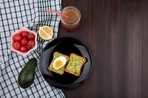 Vista superior de pão torradas com polpas de abacate e ovo com tomate em uma tigela de abacate limão rosa na toalha xadrez e superfície de madeira