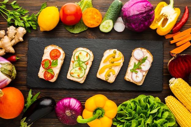 Vista superior de pedaços de pão com vegetais e arranjo de vegetais