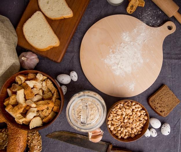 Vista superior de pedaços de pão grãos de aveia calos alho ovos faca com tábua no fundo marrom