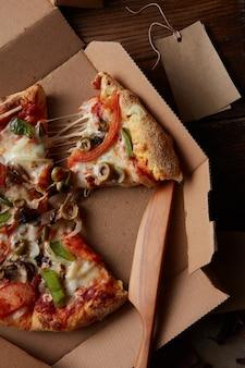 Vista superior de pedaços de pizza de queijo em uma caixa de papel sobre a mesa de madeira