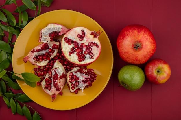 Vista superior de pedaços de romã e frutas no prato com maçã de romã e folhas na superfície do bordo
