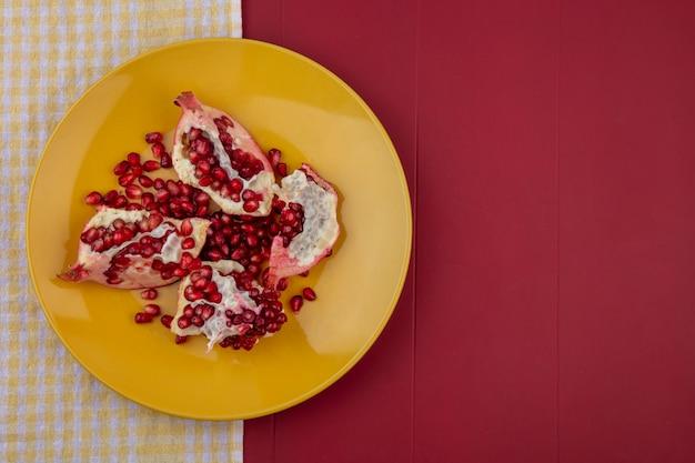 Vista superior de pedaços de romã e frutas no prato na superfície de pano e bordo xadrez