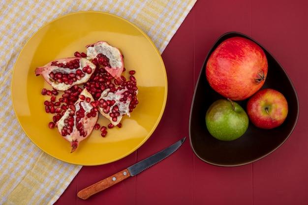 Vista superior de pedaços de romã e frutas no prato no pano xadrez com maçã de romã e faca na superfície do bordo