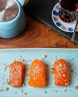 Vista superior de pedaços de sobremesa turca de doces aromatizados com avelãs em cima da mesa