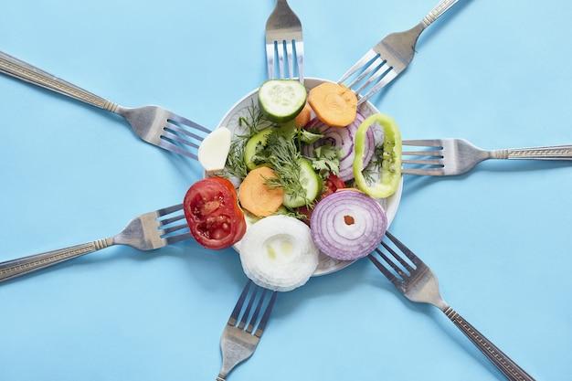Vista superior de pedaços fatiados de vegetais frescos e temperos em garfos
