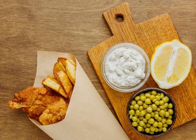 Vista superior de peixe com batatas fritas em papel embrulhado com ervilhas e rodelas de limão