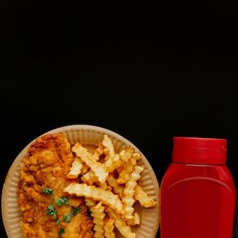 Vista superior de peixe com batatas fritas no prato com garrafa de ketchup e espaço de cópia