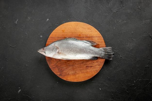 Vista superior de peixe cru fresco em uma placa de madeira redonda no espaço livre da mesa preta
