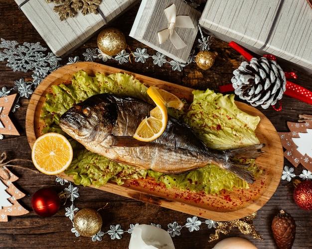 Vista superior de peixe defumado servido com alface e limão em uma porção de bambu