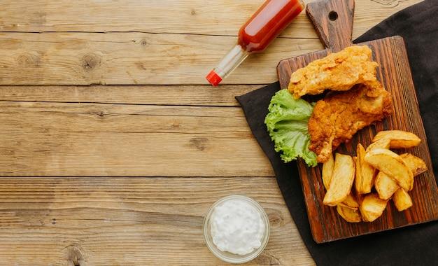 Vista superior de peixe e batatas fritas com garrafa de ketchup e espaço de cópia