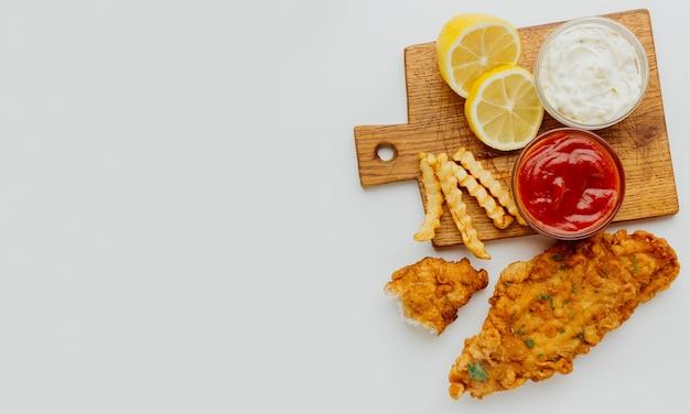 Vista superior de peixe e batatas fritas com ketchup e copie
