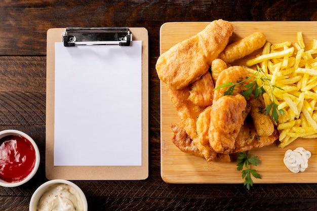 Vista superior de peixe e batatas fritas com prancheta e ketchup