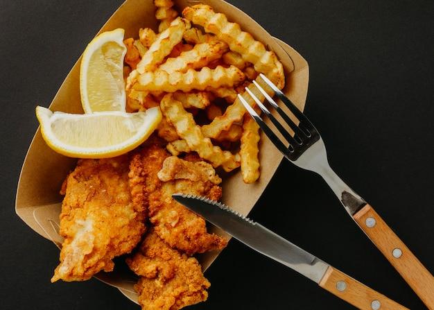 Vista superior de peixe e batatas fritas com talheres e rodelas de limão