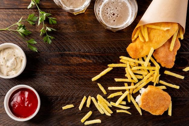 Vista superior de peixe e batatas fritas em cone de papel com cerveja