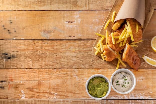 Vista superior de peixe e batatas fritas em cone de papel com espaço de cópia e molhos