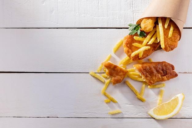 Vista superior de peixe e batatas fritas em cone de papel com espaço de cópia