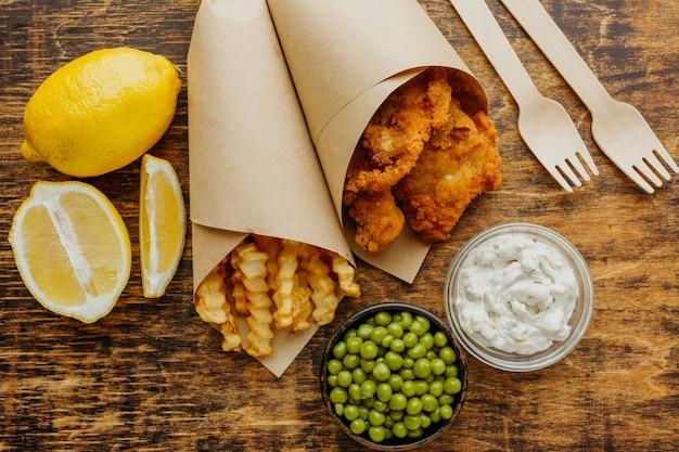 Vista superior de peixe e batatas fritas em papel embrulhado com ervilhas e talheres