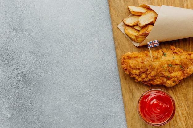 Vista superior de peixe e batatas fritas em papel embrulhado com ketchup e copie o espaço
