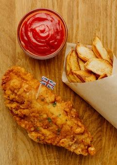 Vista superior de peixe e batatas fritas em papel embrulhado com ketchup