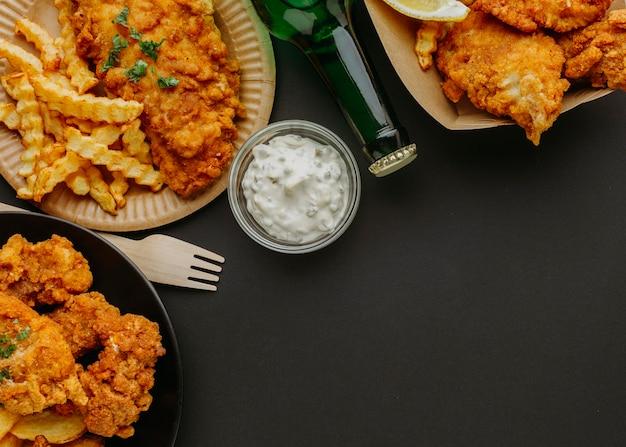 Vista superior de peixe e batatas fritas em pratos com talheres e garrafa de cerveja