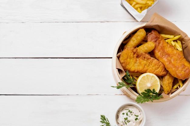 Vista superior de peixe e batatas fritas em uma tigela com limão
