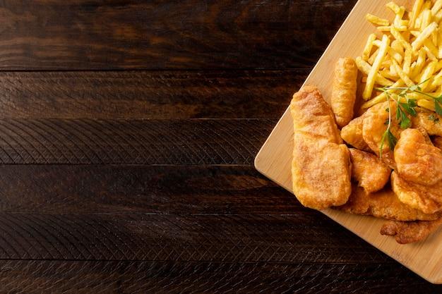 Vista superior de peixe e batatas fritas na tábua com espaço de cópia
