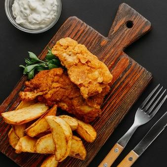 Vista superior de peixe e batatas fritas na tábua de cortar com talheres