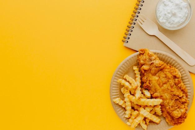 Vista superior de peixe e batatas fritas no prato com caderno e garfo