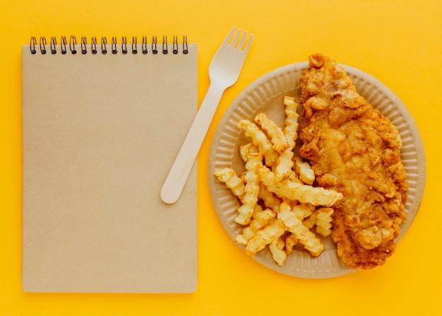 Vista superior de peixe e batatas fritas no prato com garfo e caderno