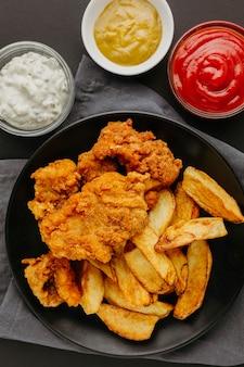 Vista superior de peixe e batatas fritas no prato com molhos