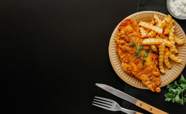 Vista superior de peixe e batatas fritas no prato com talheres e espaço de cópia