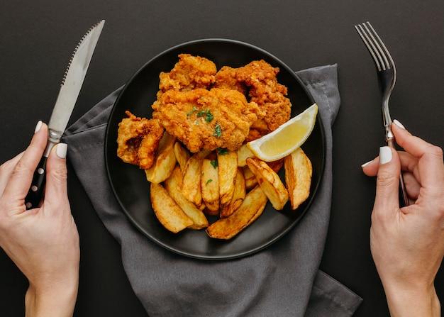 Vista superior de peixe e batatas fritas no prato com uma mulher segurando talheres