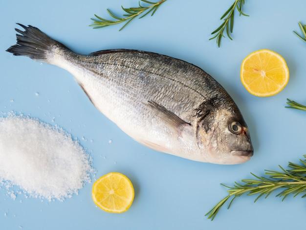 Vista superior de peixe fresco com limão e ervas