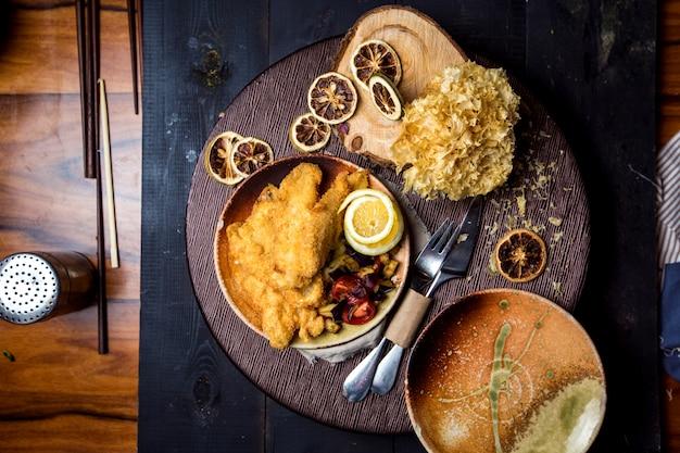 Vista superior de peixe frito crocante servido com limão, batata frita e salada de legumes