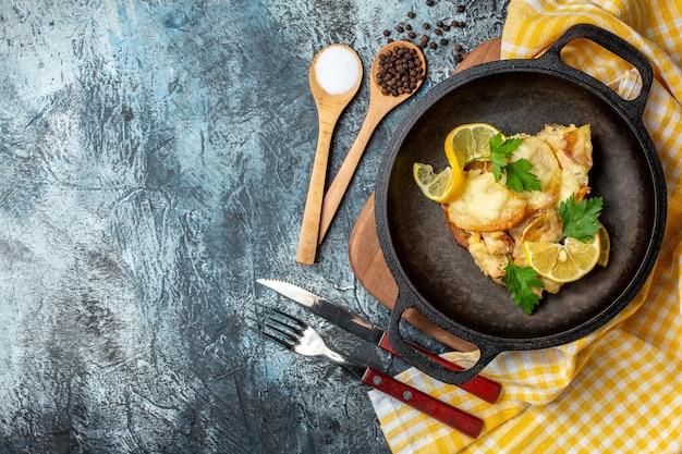 Vista superior de peixe frito em uma panela com especiarias diferentes de limão e salsa em colheres de madeira, garfo e faca em fundo cinza